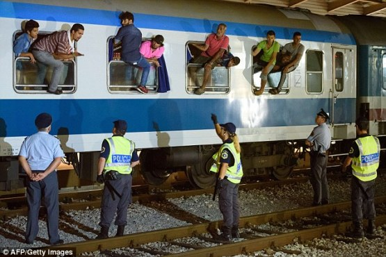 2C74290400000578-3240010-Police_officers_watch_on_as_migrants_sit_on_the_windows_of_a_tra-a-60_1442583728293
