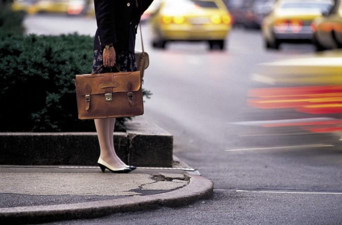 hip down of businesswoman holding a brief case, manhattan, new york, usa